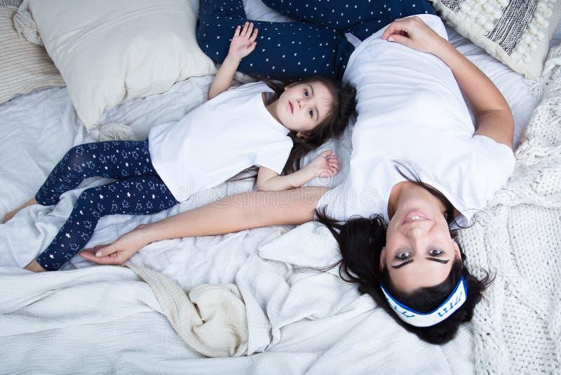 Mamma och att behandla som ett barn på sängen i sovrummet arkivfoto
