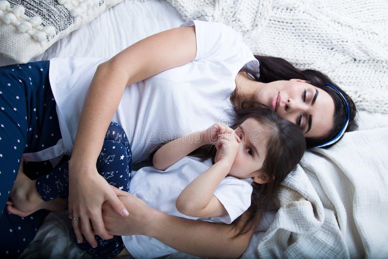 Mamma och att behandla som ett barn på sängen i sovrummet royaltyfria foton