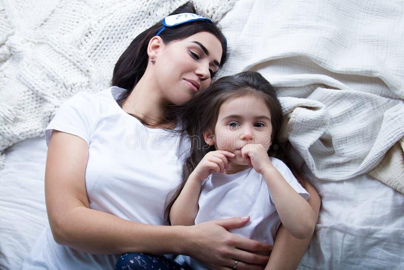 Mamma och att behandla som ett barn på sängen i sovrummet arkivbild