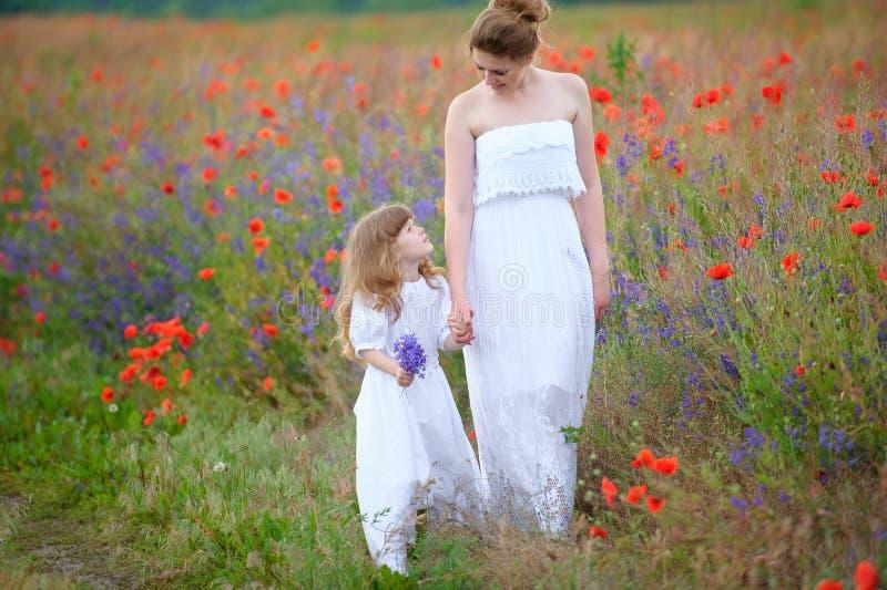 Mamma och barn som går rymma händer utomhus Två kvinnor i klänning royaltyfri bild