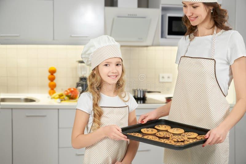 Mamma och dotter i förkläden och kockhattar som poserar med kakor arkivbild