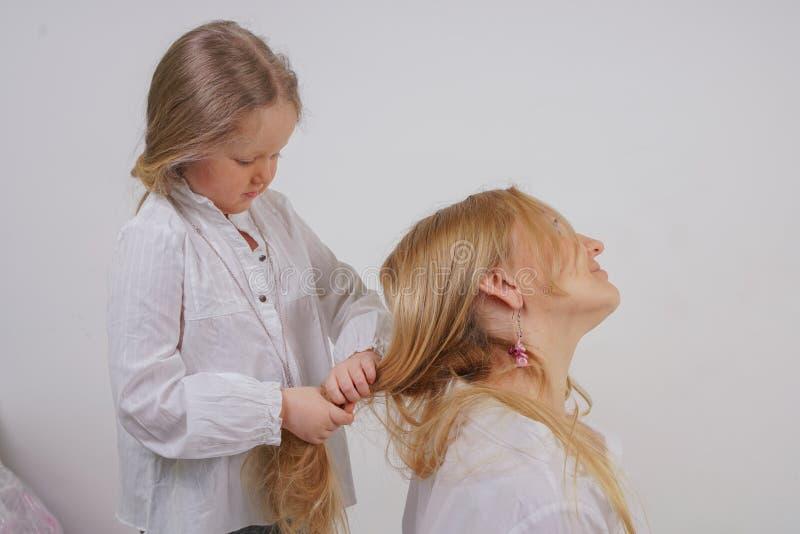 Mamma och dotter i vita skjortor med l?ngt blont h?r som poserar p? en fast bakgrund i studion en charmig familj tar omsorg av fotografering för bildbyråer