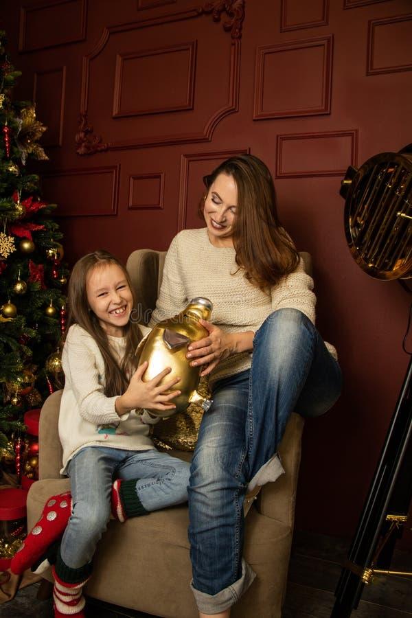 Mamma och dotter sitter i en stol nära julgranen royaltyfria bilder