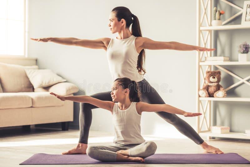 Mamma och dotter som gör yoga arkivfoto