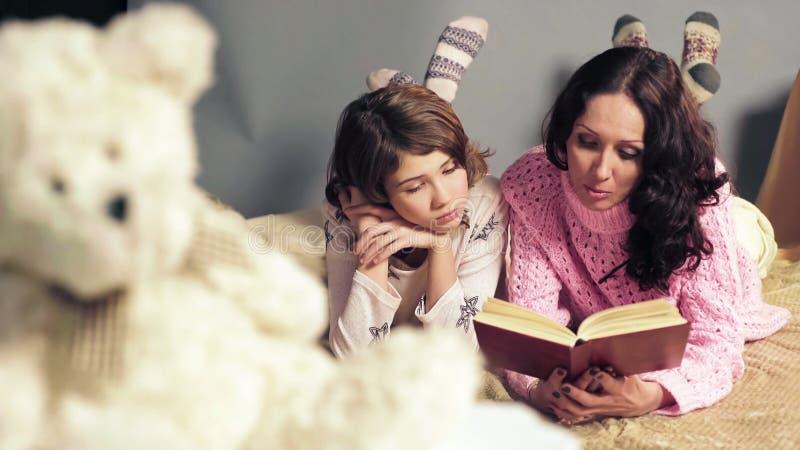Mamma och dotter som ligger bekvämt, i säng, läs- sagor och att drömma royaltyfri bild