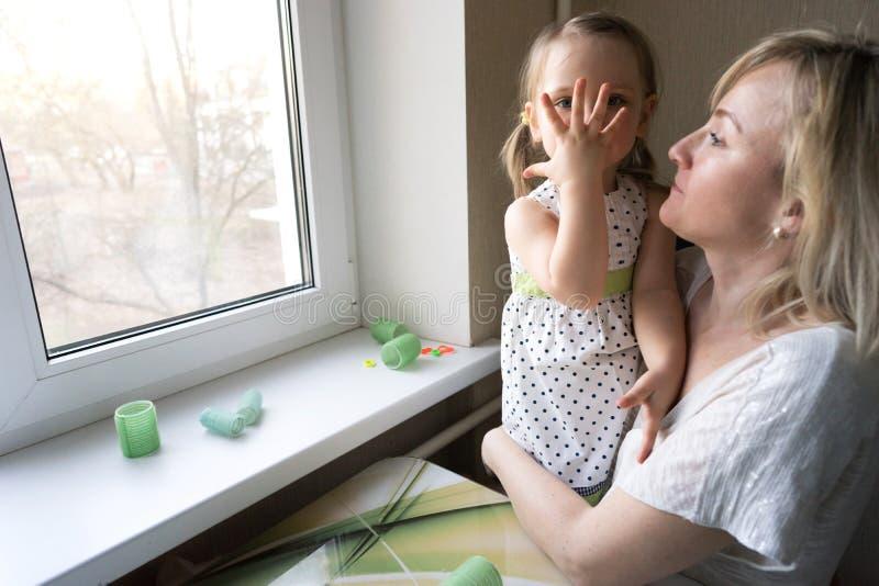 Mamma och dotter som sitter på fönstret arkivfoto