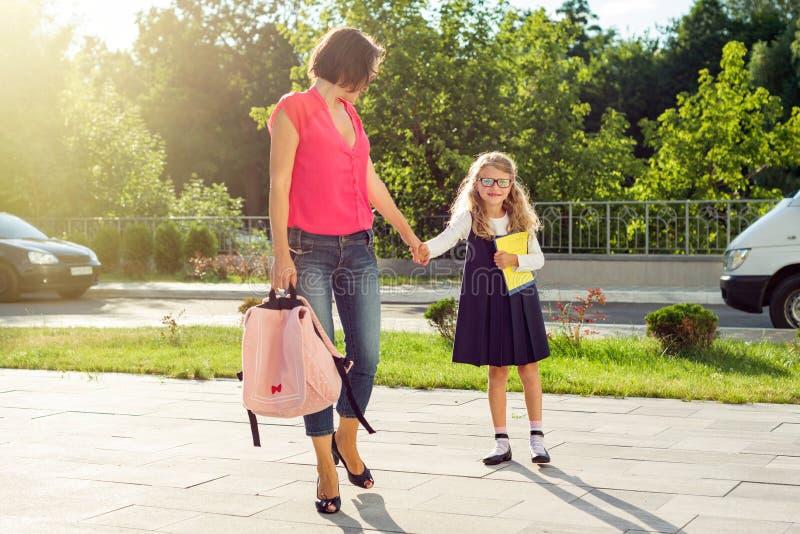 Mamma och elev av grundskolainnehavhänder fotografering för bildbyråer