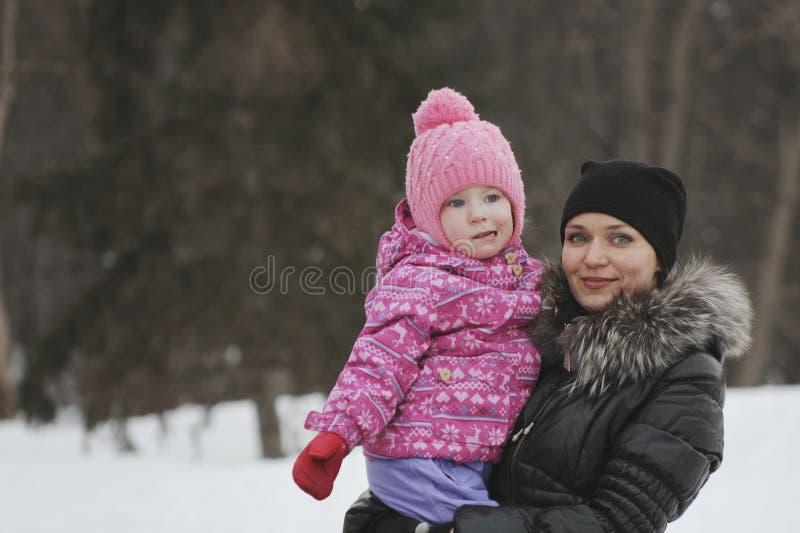 Mamma och hennes dotter i vintergatan, kvinnan som rymmer flickan i henne armar arkivbild