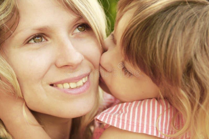 Mamma och hennes lilla dotter på gräs arkivbild