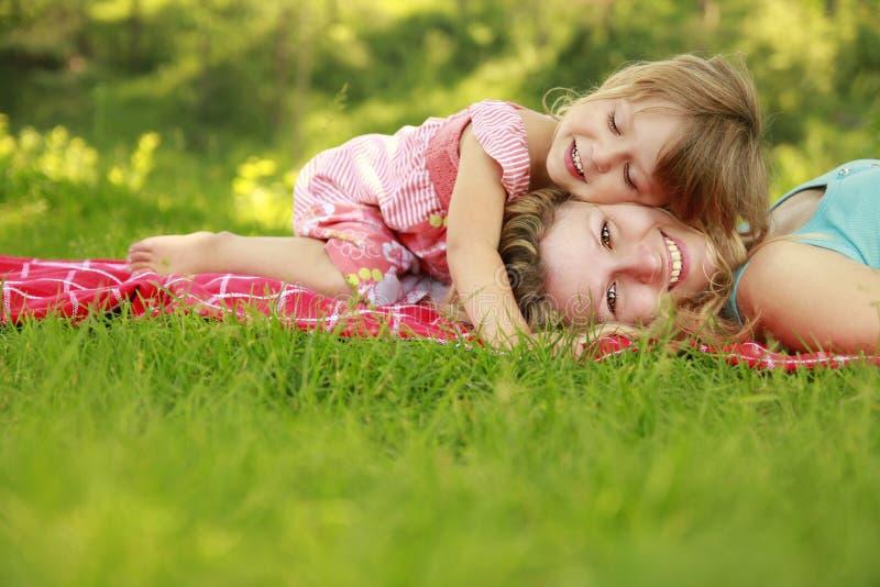 Mamma och hennes lilla dotter på gräset arkivfoto