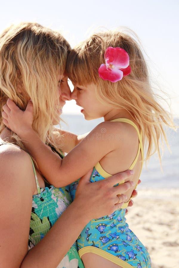 Mamma och hennes lilla dotter på stranden royaltyfri bild