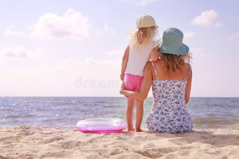 Mamma och hennes lilla dotter på stranden fotografering för bildbyråer