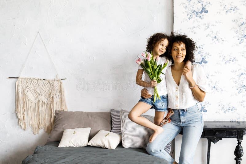 Mamma och liten gullig lockig flicka att spendera tid tillsammans och att krama och kyssa sig arkivbilder