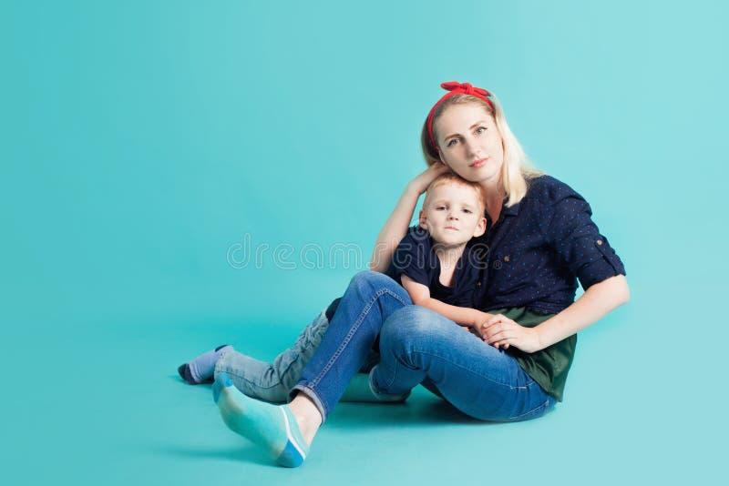 Mamma och söner, stående på blå bakgrund arkivfoto