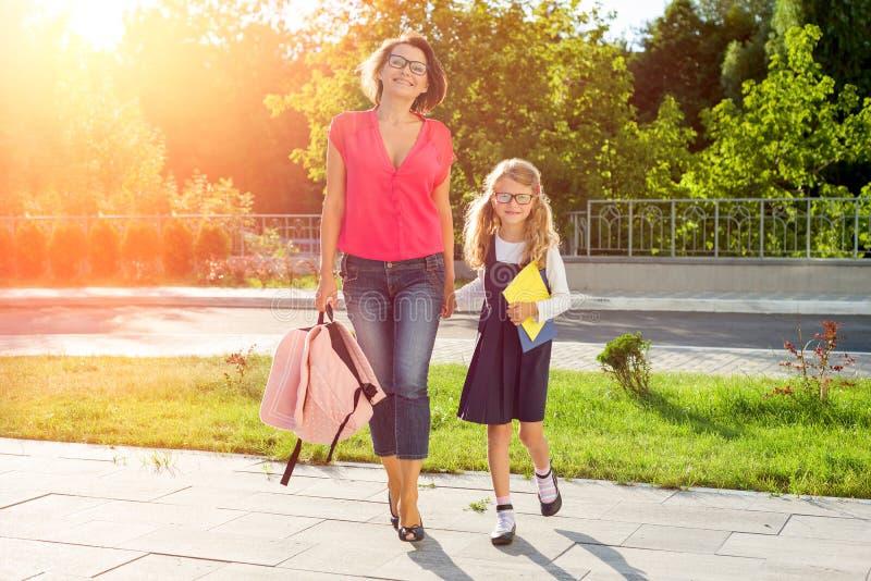 Mamma och skolflicka av grundskola för barn mellan 5 och 11 årinnehavhänder royaltyfria bilder