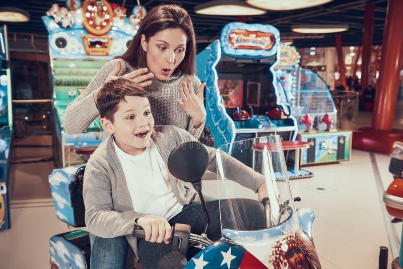 Mamma och son i nöjesfält på leksakmotorcykeln royaltyfri fotografi