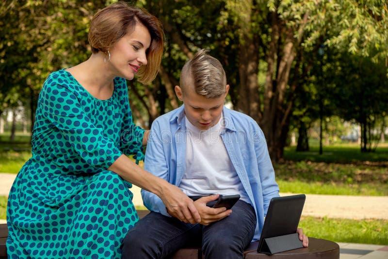 Mamma och son som använder minnestavlan och smartphonen, medan sitta på naturen Familjen spelar datoren eller söker internet royaltyfri foto