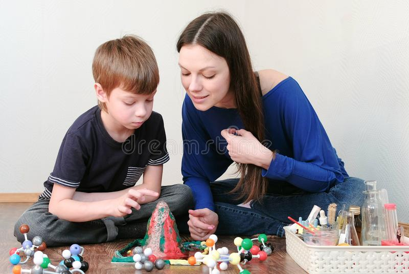Mamma och son som ser kemisk reaktion med gasutsläpp Erfarenhet med plasticinevulkan hemma fotografering för bildbyråer