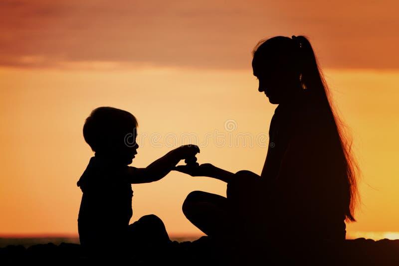 Mamma och son som spelar på stranden med stenar Solnedgångtid, silho arkivbilder