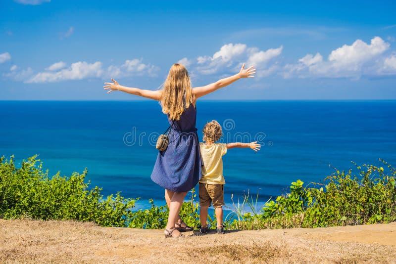 Mamma- och sonhandelsresande på en klippa ovanför stranden Tomt paradis arkivfoto