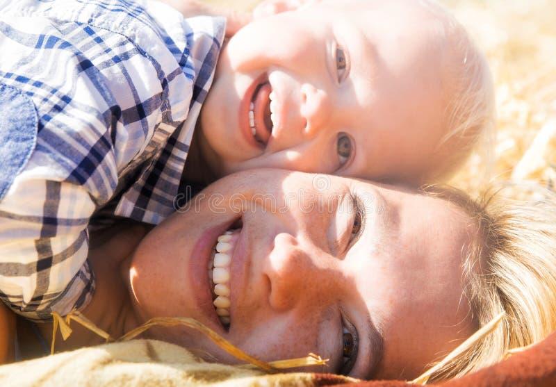 Mamma- och sonlögn på en höstack, blick på kameran och leende arkivfoto