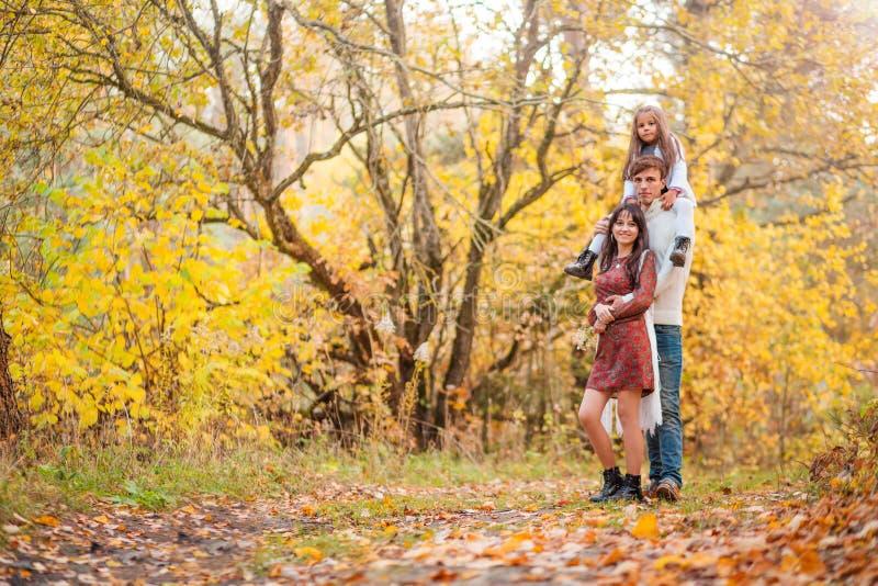 Mamma, papa en dochter de gang door de de herfst bosdochter zit op de schouders van de vader stock afbeelding