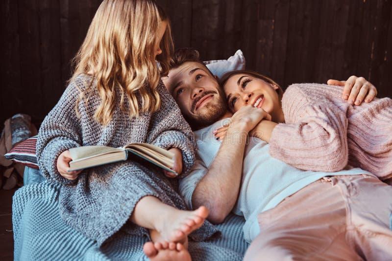 Mamma, papa en dochterlezingsverhalenboek samen terwijl het liggen op bed stock foto