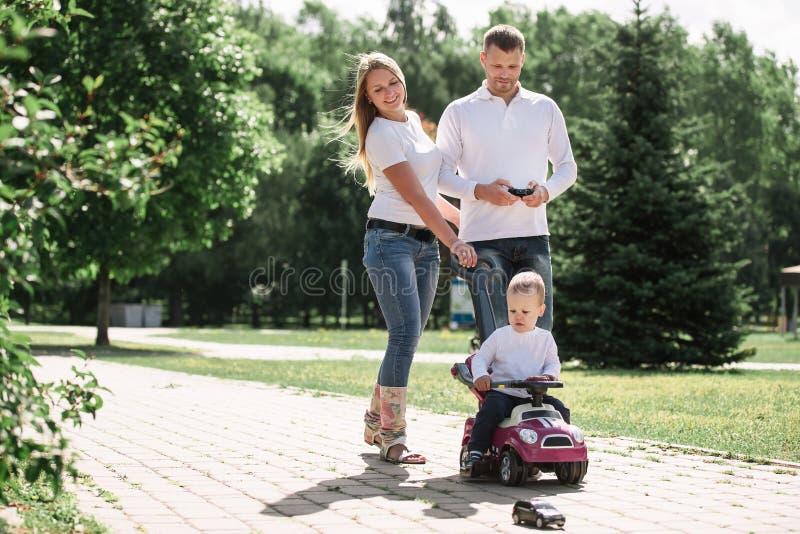 Mamma, papa, en zoon die onderaan een weg in een stadspark lopen royalty-vrije stock afbeeldingen