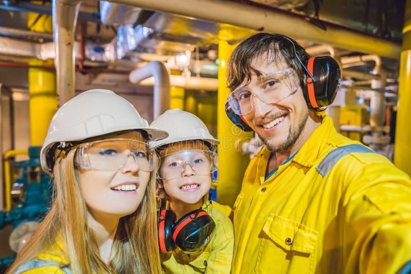 Mamma, Papa en Zoon in het geel werk eenvormig, glazen, en helm in een industriële omgeving, olieplatform of vloeibaar royalty-vrije stock afbeelding