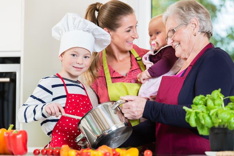 Mamma, papa, oma en kleinzoon samen in keuken die voedsel voorbereiden royalty-vrije stock foto's