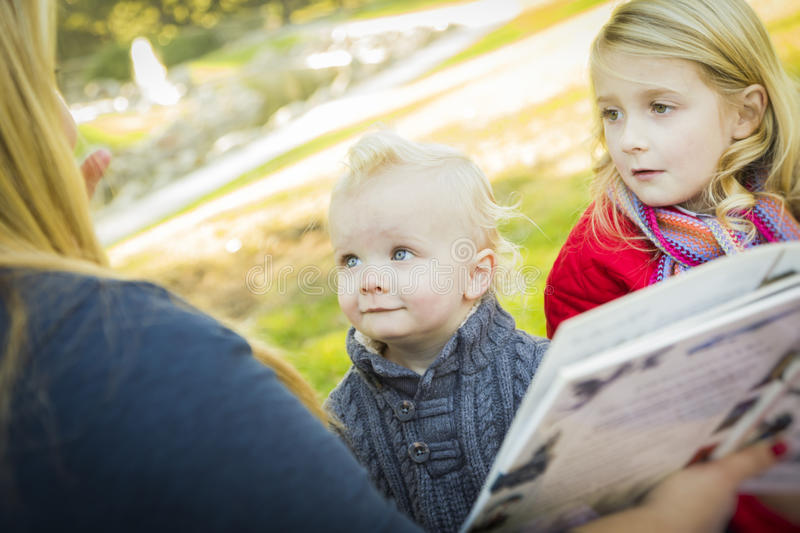 Mamma Reading a Book to Her Two Adorable Blonde Children royalty free stock images