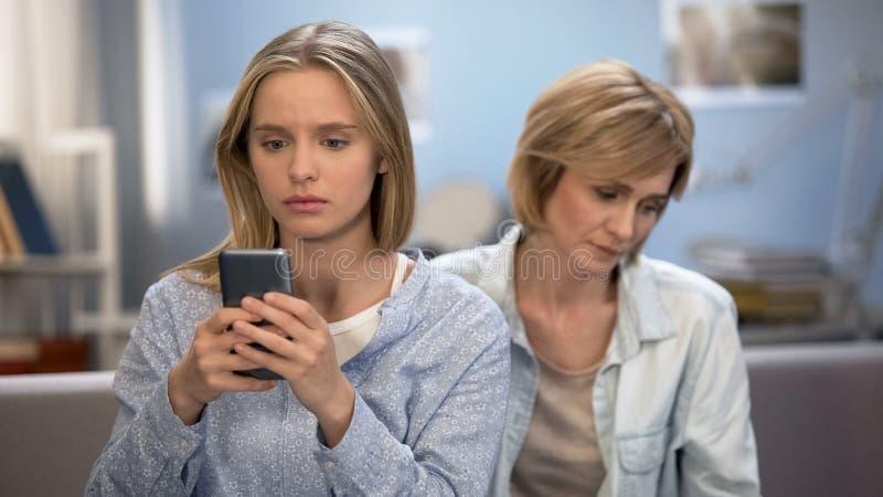 Mamma som försöker att tala till det tonårs- barnet hemma, förbindelse problem, telefonböjelse arkivfoton
