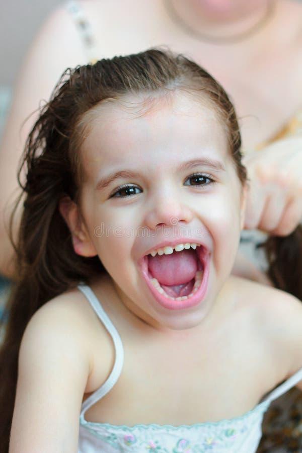 Mamma som gör en frisyr till hennes ungeflicka fotografering för bildbyråer