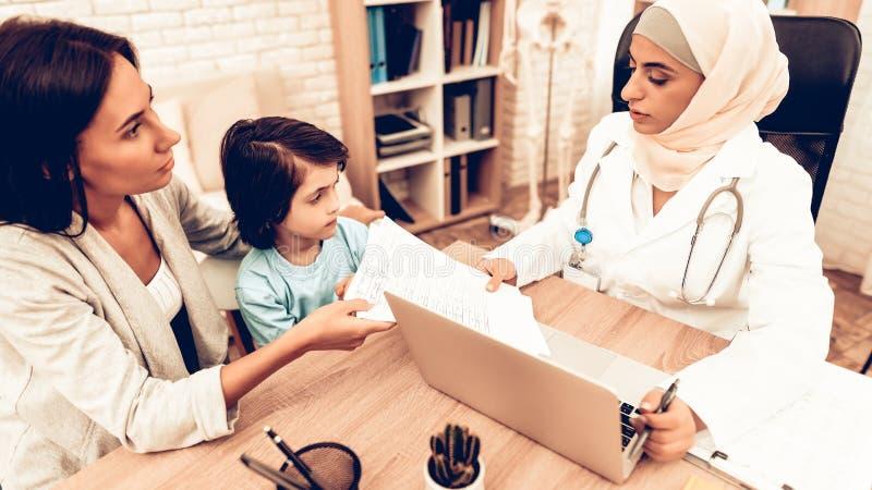 Mamma som ger sig till arabisk doktor Medical Examinations arkivbild