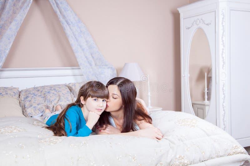 Mamma som kysser hennes härliga dotter Den lyckliga modern och dottern lägger i säng som har gyckel, ler och ser kameran arkivbild