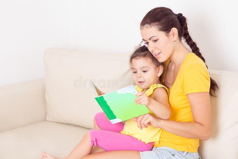 Mamma som läser en bok royaltyfri foto