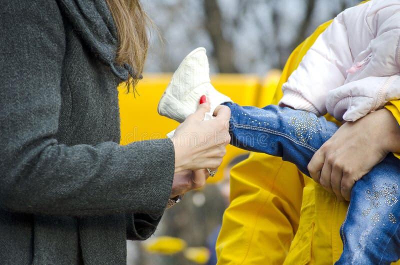 Mamma som sätter en sko på babys fot royaltyfria bilder
