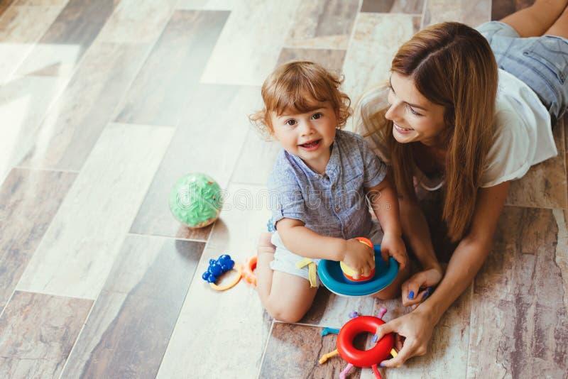 Mamma som spelar med sonen på ett golv royaltyfri bild
