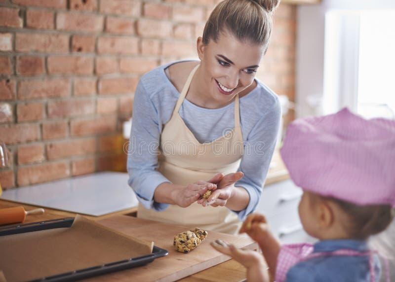 Mamma som undervisar hennes flicka hur man gör en kaka arkivfoton