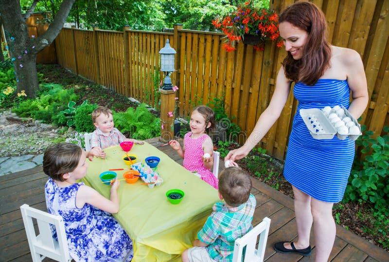 Mamma som ut räcker påskägg till målarfärg till hennes barn fotografering för bildbyråer