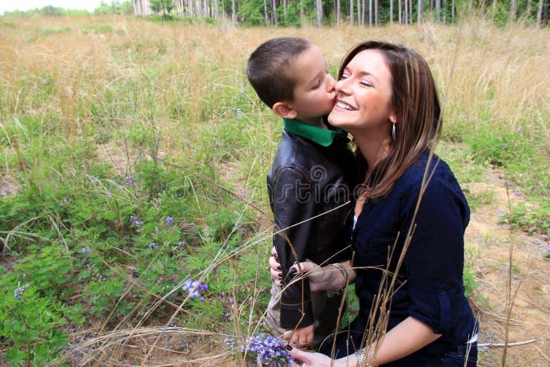 Mamma sorridente che accetta un bacio sulla guancia da suo figlio immagini stock