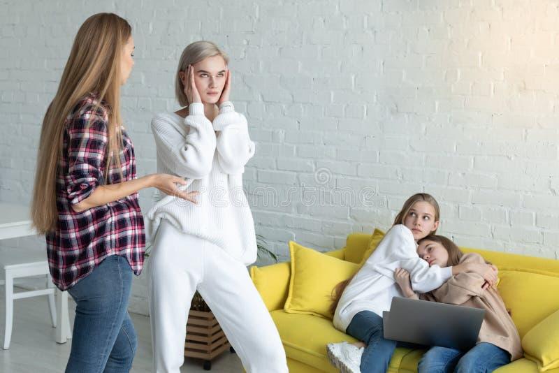 Mamma tv? i tillf?llig kl?der sv?r i n?rvaron av barn hemma arkivfoton