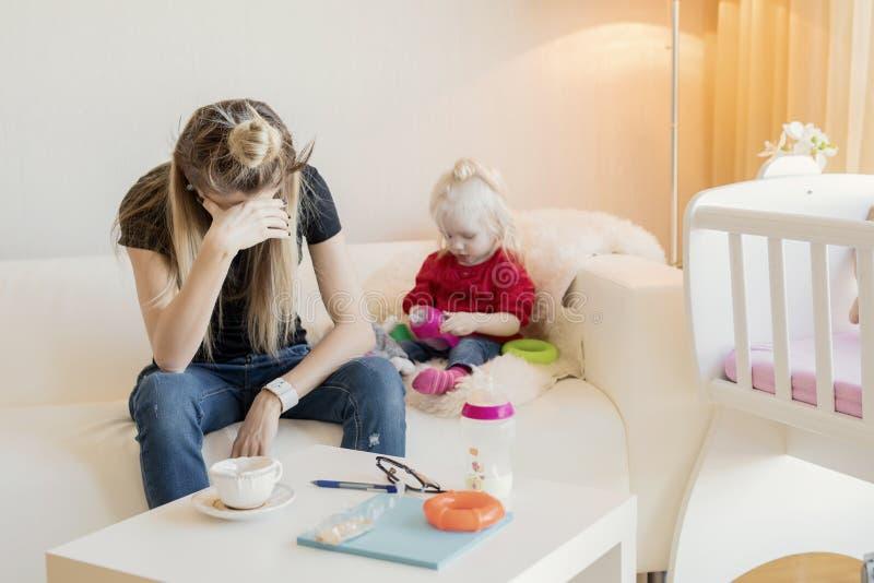 Mamma uitgeput door baby-sitting stock fotografie