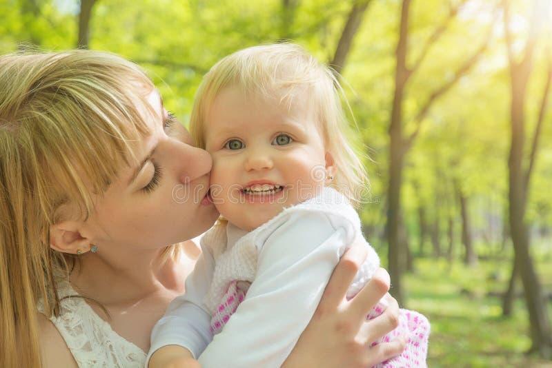 Mamma un giorno soleggiato che gioca con sua figlia nel parco verde fotografie stock