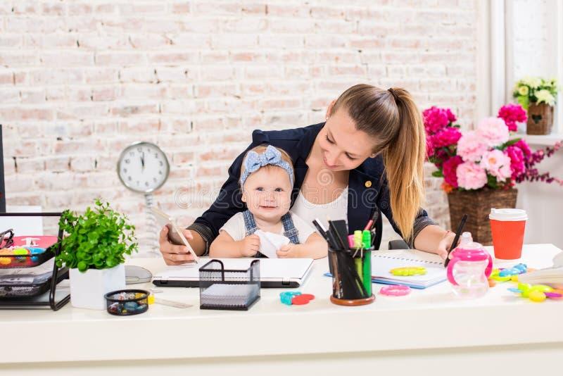 Mamma und Geschäftsfrau, die zu Hause mit Laptop-Computer arbeiten und mit ihrem Baby spielen lizenzfreies stockbild