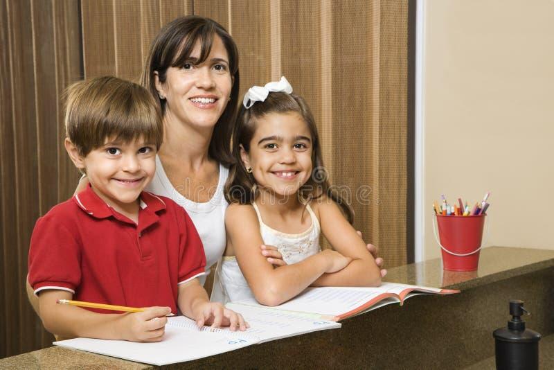 Mamma und Kinder mit Heimarbeit. stockbild