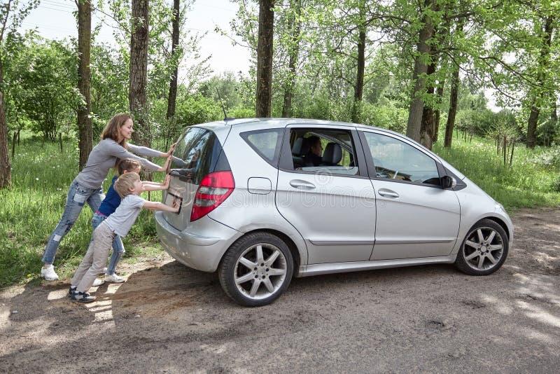 Mamma, zoon en dochter die een defecte auto duwen stock afbeelding