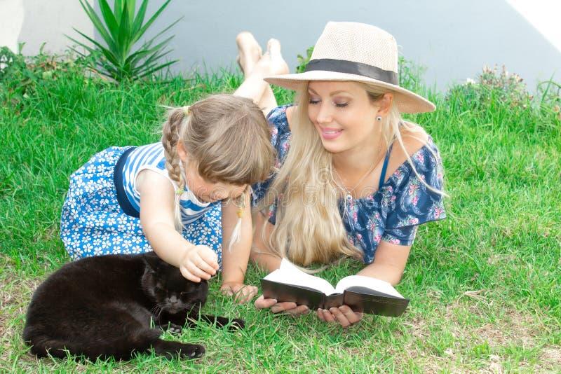 Mammablondinen i en hatt och hennes dotter ligger på gräset och läser en bok, lycklig familj fotografering för bildbyråer