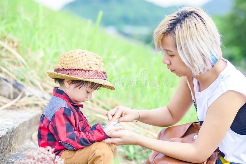 Mammabrukssilkespapper som gör ren barnhanden i parkera En barnkläderhatt arkivfoto