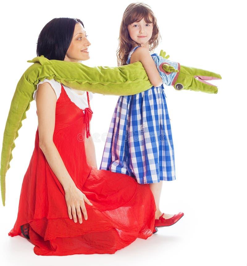 Mammadochter en een stuk speelgoed krokodil stock afbeelding
